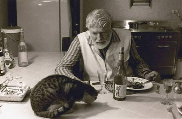 Эрнест Хэмингуэй и кот за столом