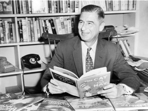 Ted Geisel (Dr Seuss) seated at desk covered with his uniquely humorous children's books