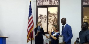 Madam Royce (L) displays a copy of the books as Ambassador Elder and Liberian officials look on with excitement